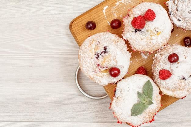 Zelfgemaakte fruitmuffins bestrooid met poedersuiker en verse frambozen op houten snijplank. kerst snoep en gebak. bovenaanzicht met kopie ruimte.