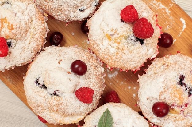 Zelfgemaakte fruitmuffins bestrooid met poedersuiker en verse frambozen op houten snijplank. kerst snoep en gebak. bovenaanzicht.