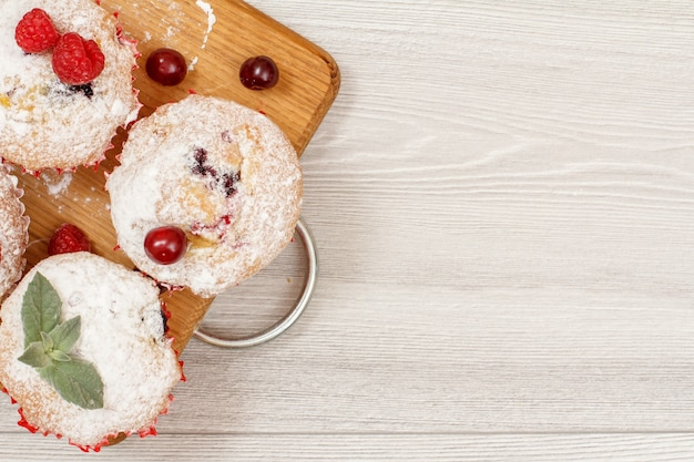 Zelfgemaakte fruitmuffins bestrooid met poedersuiker en verse frambozen op houten snijplank.