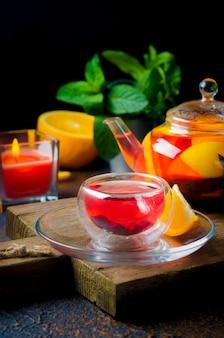 Zelfgemaakte gearomatiseerde fruitthee in glazen beker en theepot met vers gezette sinaasappel- en citroenschijfjes, bessen, munt en honing op donkere rustieke achtergrond. warme herfst- of winterdrank. thee ceremonie