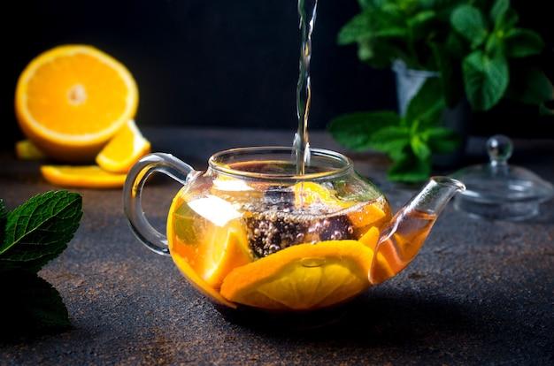 Zelfgemaakte gearomatiseerde fruitthee met sinaasappel- en citroenschijfje, bes, munt en honing in glazen theepot op donkere rustieke achtergrond. warme herfst- of winterdrank. heet water stroomt in een waterkoker.