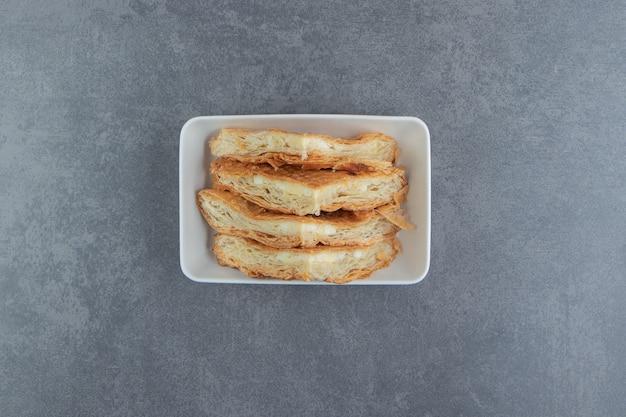 Zelfgemaakte gebakjes met kaas op witte plaat.