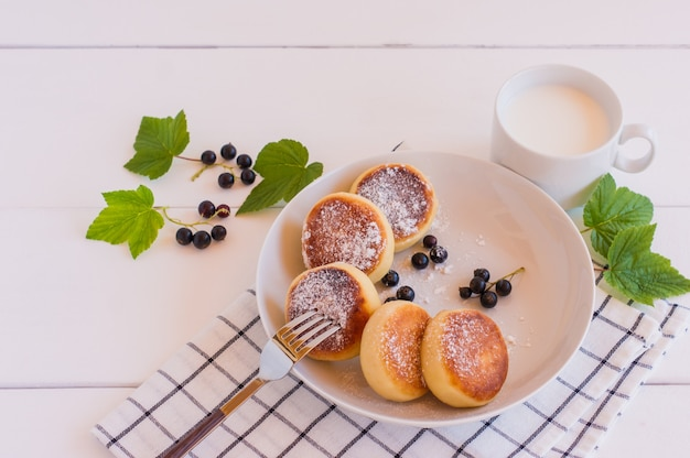 Zelfgemaakte gebakken cheesecakes met melk en bessen, close-up