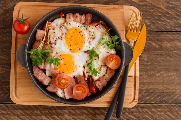 Zelfgemaakte gebakken eieren met spek en tomaten in een koekenpan op houten achtergrond. klassiek ontbijt. bovenaanzicht.