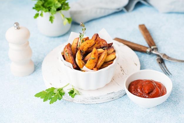 Zelfgemaakte gebakken gebakken aardappelen met kruiden en rode saus