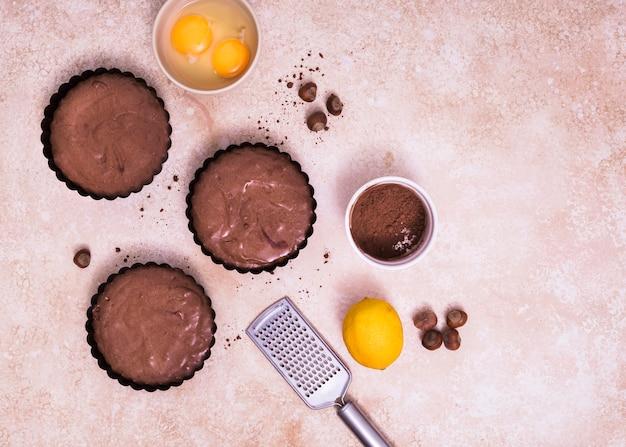 Zelfgemaakte gebakken taarten met eigeel; hazelnoot; hele citroen en handrasp tegen gestructureerde achtergrond