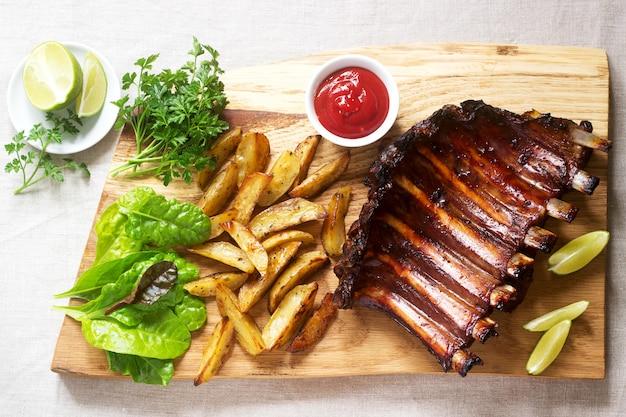 Zelfgemaakte gebakken vleesribbetjes geserveerd met frietjes, kruiden, limoen en ketchup op een houten bord. rustieke stijl.