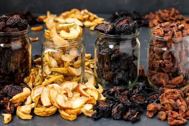 Zelfgemaakte gedroogde appels, pruimen, peren en abrikozen in glazen potten, traditioneel drogend fruit thuis, om vitamines te bewaren om te koken, horizontale oriëntatie