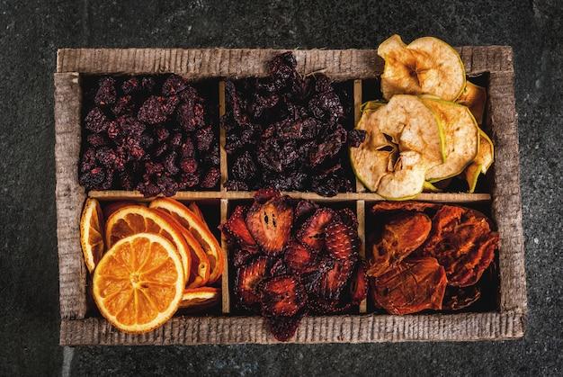 Zelfgemaakte gedroogde bessen en fruit, oogst voor de winter: abrikozen, appels, aardbeien, frambozen, kersen, sinaasappels. in oude houten doos, op zwarte stenen tafelblad weergave