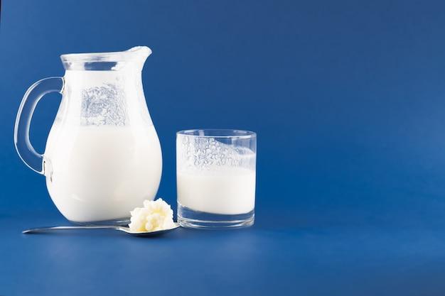 Zelfgemaakte gefermenteerde drankkefir met kefirkorrels op een trendy blauwe achtergrond, concept van natuurlijk gefermenteerd voedsel en darmgezondheid