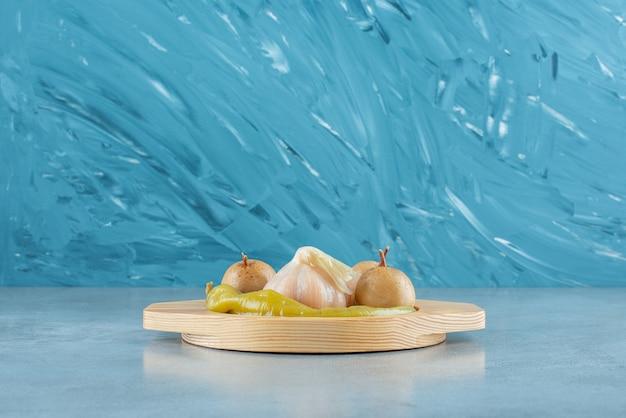 Zelfgemaakte gefermenteerde groenten op een houten bord, op de marmeren tafel.