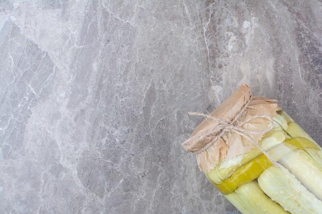 Zelfgemaakte gefermenteerde komkommers in glazen pot.