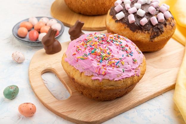 Zelfgemaakte geglazuurde en versierde pasen-taarten met chocolade-eieren en konijnen op een witte betonnen achtergrond en geel textiel.