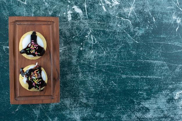 Zelfgemaakte geglazuurde koekjes op een houten bord, op het blauwe oppervlak