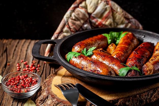 Zelfgemaakte gegrilde varkensvlees barbecue worstjes in een ijzeren pan
