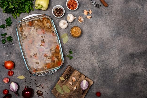 Zelfgemaakte gelei met vlees. aspic gevogelte en rundvlees, traditionele russische en oekraïense schotel op een grijze achtergrond met mosterd. kopieer ruimte