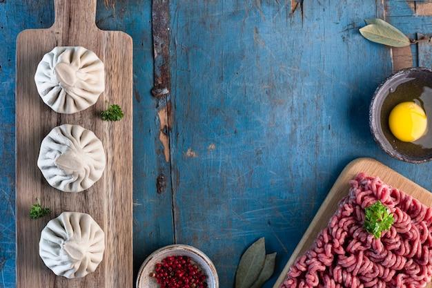 Zelfgemaakte georgische khinkali en ingrediënten voor het koken op een oude houten blauwe tafel. kopieer ruimte. bovenaanzicht