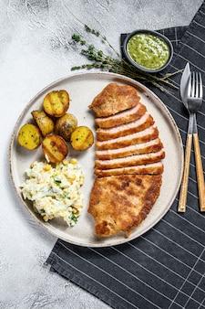 Zelfgemaakte gepaneerde duitse weiner schnitzel met aardappelen en salade.