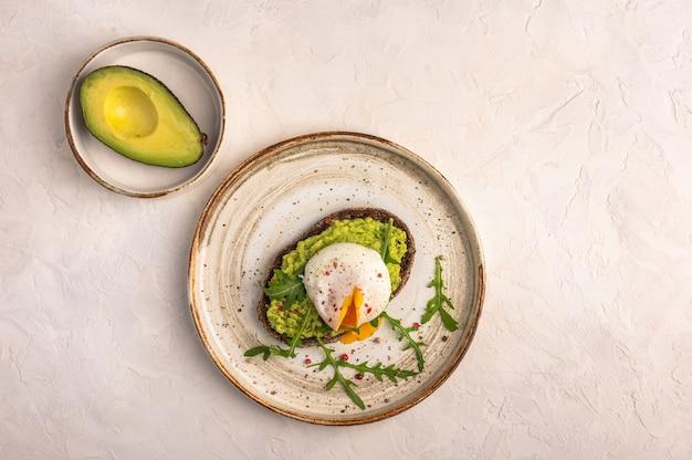Zelfgemaakte gepocheerde eiertoost met avocado, gezouten zalm, rucola en roggebrood op een keramische plaat, bovenaanzicht. gezond voedselconcept