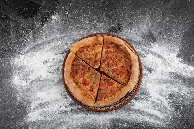 Zelfgemaakte gesneden pizza op bruine plaat op zwarte ondergrond