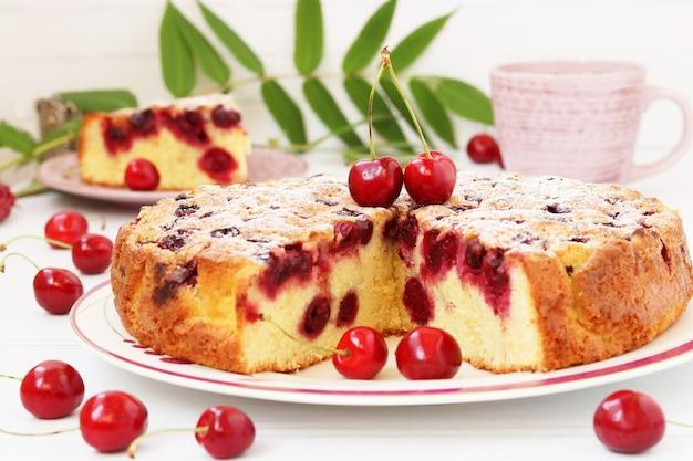 Zelfgemaakte gesneden taart met kersen bevindt zich op een bord op een witte achtergrond met een kopje koffie. detailopname