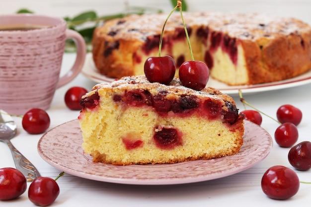 Zelfgemaakte gesneden taart met kersen bevindt zich op een bord op een witte achtergrond met een kopje koffie.
