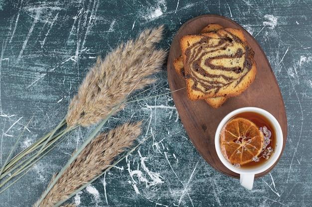 Zelfgemaakte gestreepte cake en kopje thee op houten plaat.