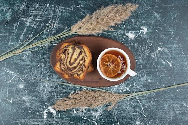 Zelfgemaakte gestreepte cake en kopje thee op marmeren achtergrond. hoge kwaliteit foto