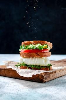 Zelfgemaakte gezonde sandwich met volkoren brood, gepocheerd ei, komkommer, tomaat en micro herbs waterkers salade op houten bord.