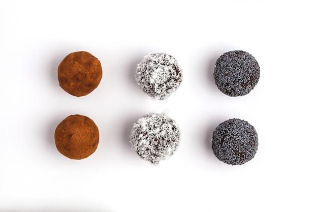 Zelfgemaakte gezonde veganist rauwe energie ballen met johannesbrood, papaver en kokosnoot geïsoleerd op een witte achtergrond, bovenaanzicht