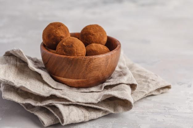 Zelfgemaakte gezonde veganistisch rauwe energie truffel ballen met johannesbrood in houten kom. gezond veganistisch eten concept.