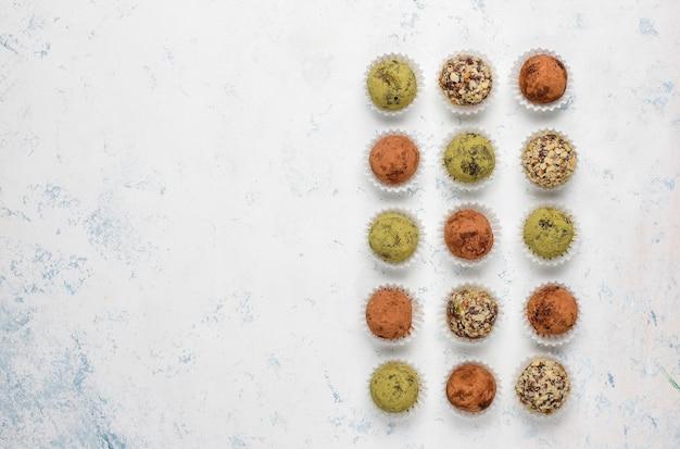 Zelfgemaakte gezonde veganistische truffelballetjes met rauwe energie met dadels en walnoten, matchapoeder, cacaopoeder