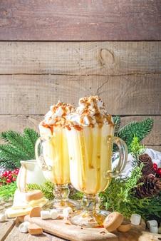 Zelfgemaakte gezouten karamel eierpunch of witte warme chocolademelk drankje, met karamelsaus, slagroom en marshmallow, op houten backgroundwith winter kerstversiering kopie ruimte