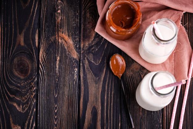 Zelfgemaakte gezouten karamel op een donkere tafel met een mooie zwarte lepel en melk.