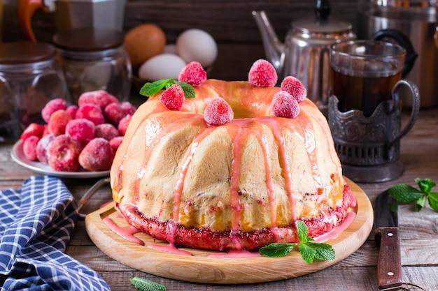 Zelfgemaakte gistcake met aardbeienjam op een oude houten tafel