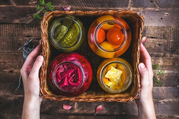 Zelfgemaakte glazen potten van ingelegde verse komkommers, sappige tomaten, zoete courgette in een rieten doos op een houten achtergrond.