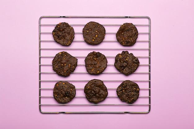 Zelfgemaakte glutenvrije chocoladeschilferkoekjes met ontbijtgranen, noten en biologische cacao. koekjes en gebakjes van roggemeel op een gekleurde achtergrond. glutenvrij concept