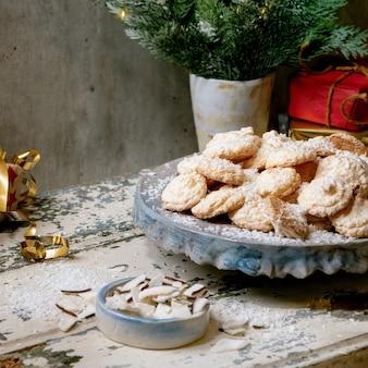 Zelfgemaakte glutenvrije kerstkoekjes met kokosvlokken op keramische plaat op oude houten tafel met kerstcadeaus en decoraties. vierkante afbeelding