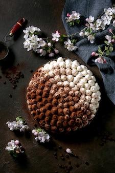 Zelfgemaakte glutenvrije tiramisu traditioneel italiaans dessert besprenkeld met cacaopoeder met bloeiende appelboom, blauw textiel servet en koffiebonen over donkere textuur oppervlak. bovenaanzicht, plat gelegd