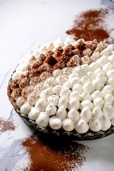 Zelfgemaakte glutenvrije tiramisu traditioneel italiaans dessert besprenkeld met cacaopoeder over witte marmeren tafel