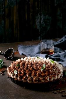 Zelfgemaakte glutenvrije tiramisu traditioneel italiaans dessert besprenkeld met cacaopoeder versierd met muntblaadjes, glas whisky, blauw textiel servet en koffiebonen over donkere textuur oppervlak.