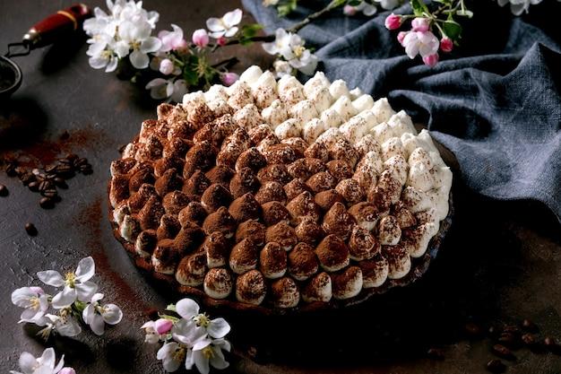 Zelfgemaakte glutenvrije tiramisu traditioneel italiaans dessert bestrooid met cacaopoeder versierd met bloeiende appelboom, blauw textiel servet en koffiebonen over donkere textuur oppervlak.