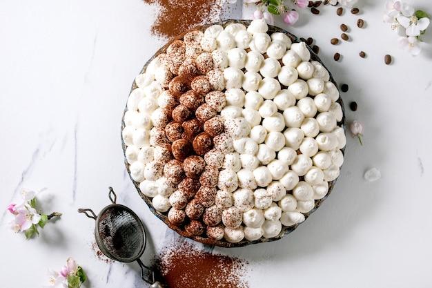 Zelfgemaakte glutenvrije tiramisu traditioneel italiaans dessert bestrooid met cacaopoeder versierd met bloeiende appelboom en koffiebonen over wit marmeren oppervlak. bovenaanzicht, plat gelegd. ruimte kopiëren
