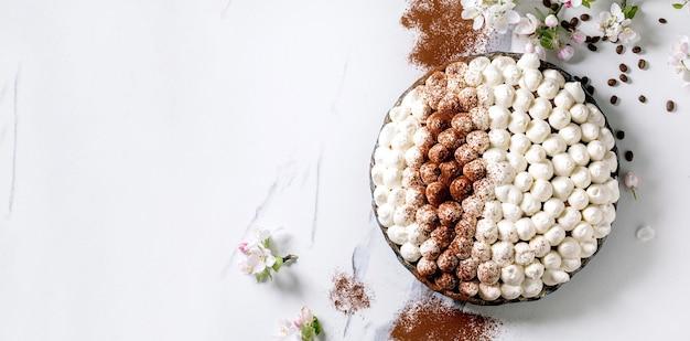 Zelfgemaakte glutenvrije tiramisu traditioneel italiaans dessert bestrooid met cacaopoeder versierd met bloeiende appelboom, koffiebonen over wit marmeren oppervlak. bovenaanzicht. ruimte kopiëren. bannerformaat