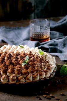 Zelfgemaakte glutenvrije tiramisu traditioneel italiaans dessert bestrooid met cacaopoeder versierd met muntblaadjes, glas whisky, blauw textiel servet en koffiebonen. donker oppervlak. detailopname