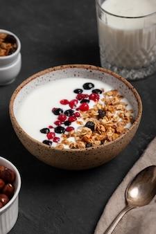 Zelfgemaakte granola-ontbijtkom met natuurlijke yoghurtbessen, hazelnoot en amandel op donkere achtergrond