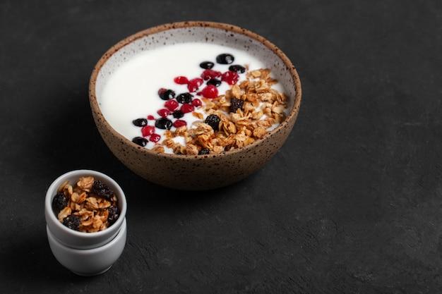 Zelfgemaakte granola-ontbijtkom met natuurlijke yoghurtbessen, hazelnoot en amandelen op donkere achtergrond