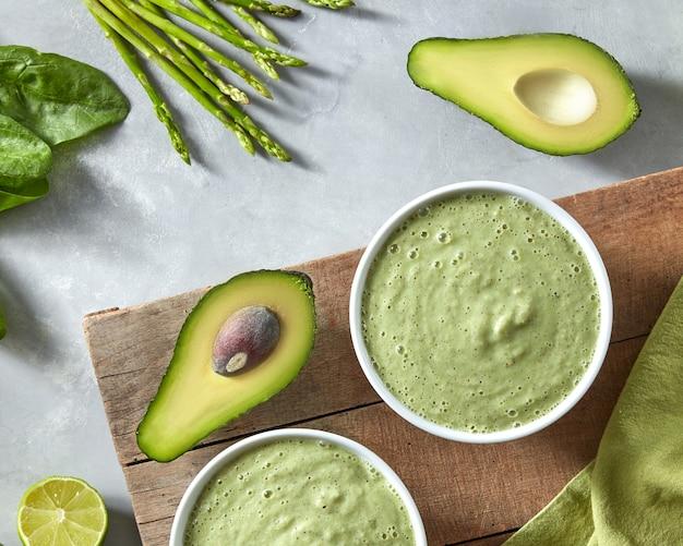 Zelfgemaakte groene gezonde smoothies van spinazie, avocado en asperges in een kom op een houten bord met een groen servet op een betonnen muur