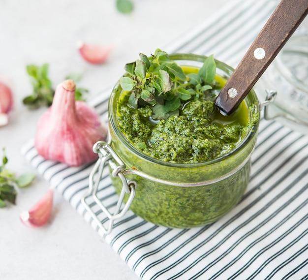 Zelfgemaakte groene pestosaus met basilicum en knoflook in een glazen pot