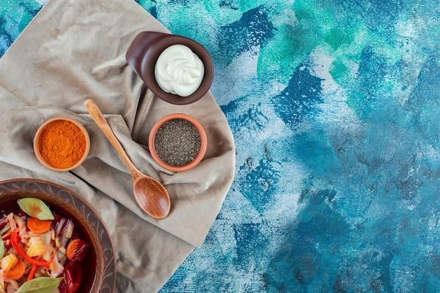 Zelfgemaakte groentesoep op een bord op stukjes stof, op de blauwe achtergrond.